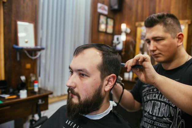 Barber shop, a man with a beard cut hairdresser Premium Photo