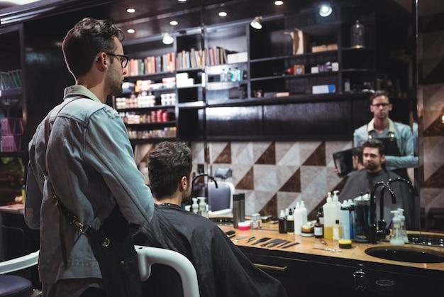 Barbiere che mostra all'uomo il suo taglio di capelli nello specchio Foto Gratuite