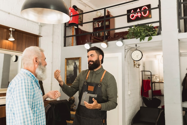 Barber talking with elderly client in hair salon Free Photo
