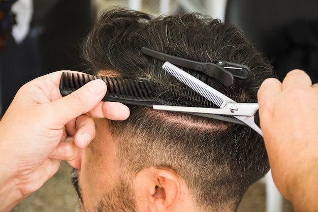 Barber using scissors and comb to cut the man's hair Free Photo