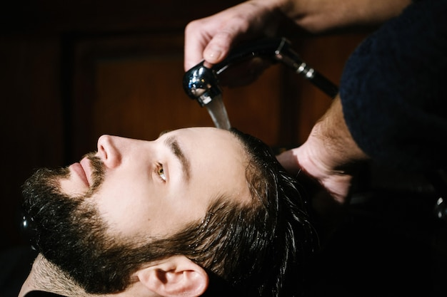 Barber washes hair of bearded man Free Photo