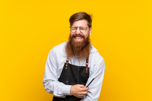 Barber with long beard in an apron over isolated yellow background Premium Photo
