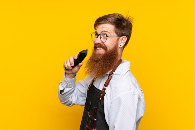 Barber with long beard in an apron over isolated yellow wall Premium Photo