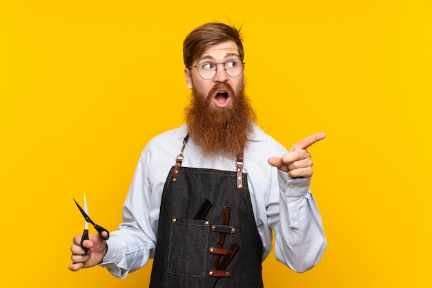 Barber with long beard in an apron yellow surprised and pointing finger to the side Premium Photo