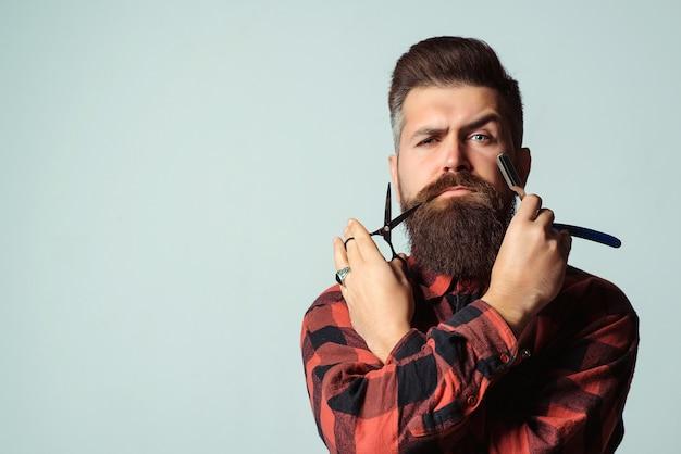 Парикмахерская с бритвой и ножницами над синей стеной. брутальный мужчина держит профессиональные инструменты. парикмахерская. Premium Фотографии