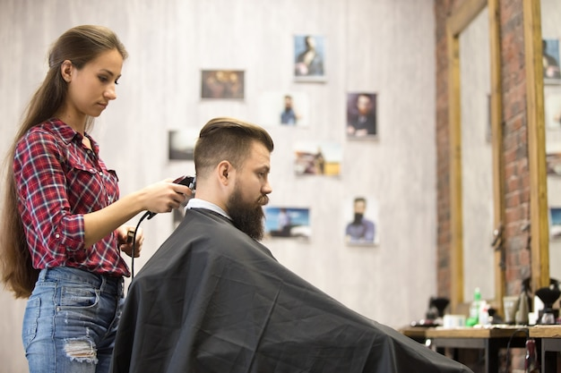 Barber woman serving client in barbershop Free Photo