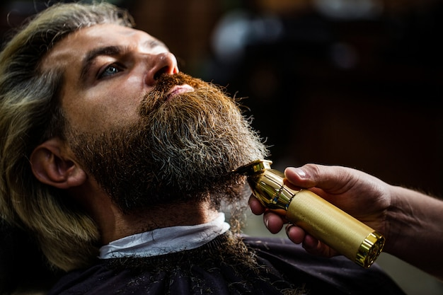 Barber works with a beard clipper. hipster client getting haircut. hands of a hairdresser with a beard clipper, closeup. Premium Photo