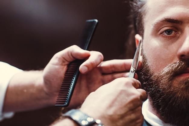 Парикмахерская. бородатый образцовый человек и парикмахер с ножницами. Premium Фотографии