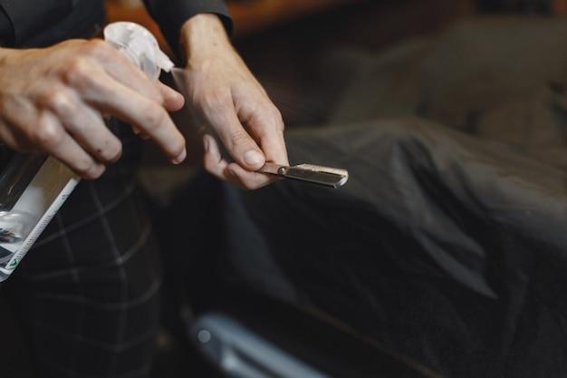 Barbiere. il primo piano del barbiere tiene il rasoio per radersi la barba Foto Gratuite