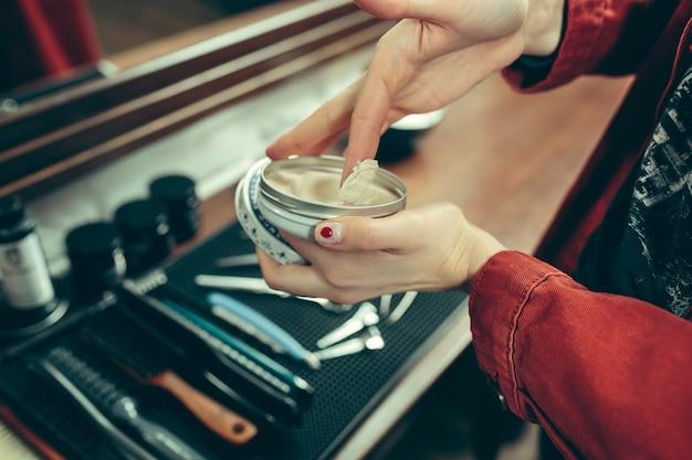 Парикмахерская. женский парикмахер в салоне. гендерное равенство. женщина в мужской профессии. руки крупным планом Бесплатные Фотографии