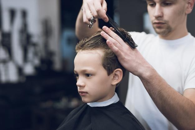 Barbershop hairdresser make boy haircut Premium Photo