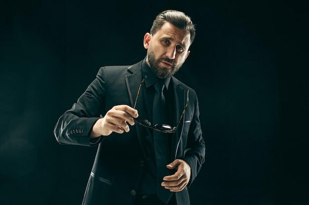 スーツを着た男。黒の背景にスタイリッシュなビジネスマン。美しい男性の肖像画。若い感情的な男。 無料写真