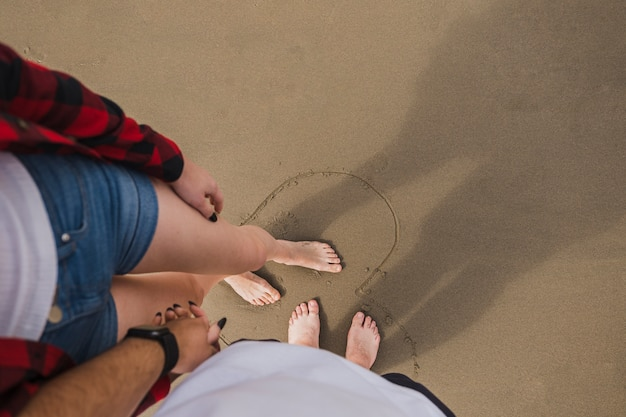 Bare feet couple holding hands on beach Free Photo