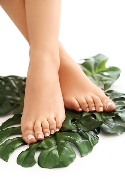 Босые ноги на листьях. концепция ухода за ногами и педикюра Бесплатные Фотографии