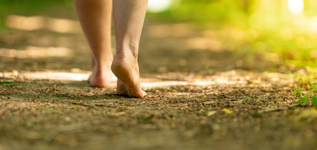 Bare feet of a woman walking along a trail in the woods Premium Photo