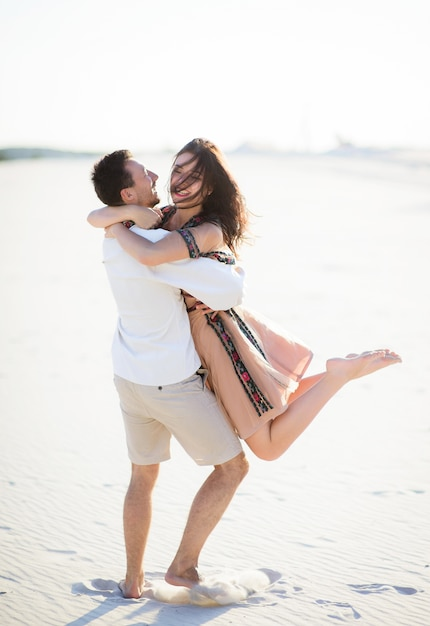 Barefooted couple in bright embroidered clothing walks on a white sand Free Photo