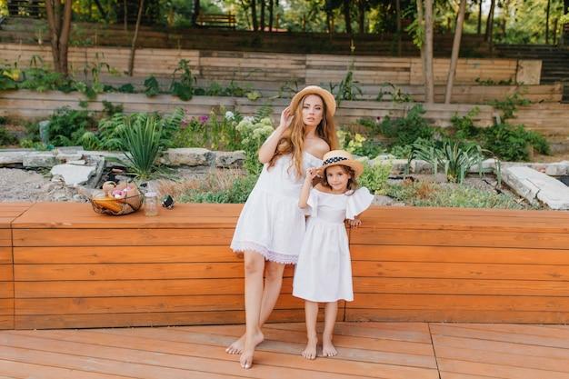 自然の上の木の床に立っている白いドレスを着た裸足のスリムな女性と彼女の娘。ピクニックの後、小さな姪と一緒に公園でポーズをとっている格好良い格好の良い女性。 無料写真