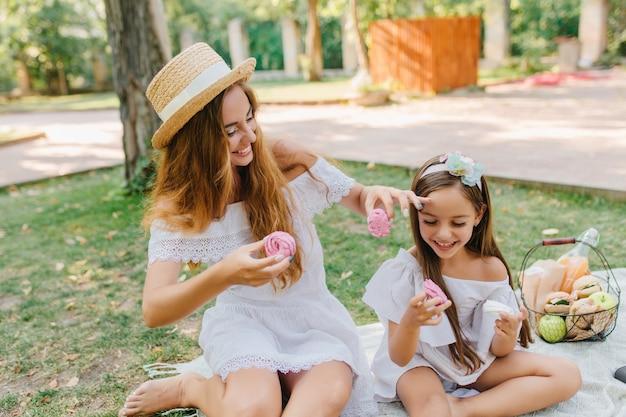 Donna a piedi nudi in cappello con nastro bianco che si siede sulla coperta vicino alla figlia e che mangia i biscotti sorridendo. ritratto esterno della famiglia felice scherzando e scherzando durante il picnic. Foto Gratuite