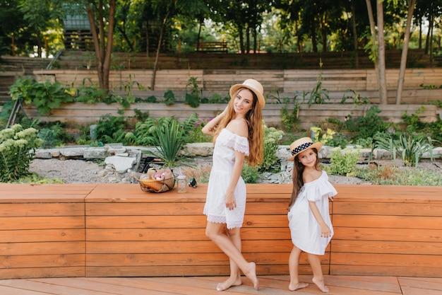 花壇の前で背中合わせに立っている裸足の若い女性と少女。夏の公園で同様の服を着ているスタイリッシュな母と娘の屋外の全身像。 無料写真