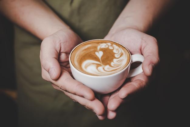 Barista handling hot cafe latte. Free Photo