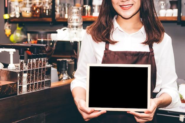 Barista holding chalkboard  in coffee shop restaurant Premium Photo