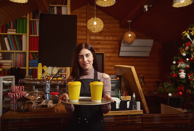 Barista holds a tray with yellow takeaway cardboard cups of coffee and showing it at camera Premium Photo