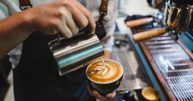 バリスタがラテアートを作り、一杯の牛乳とコーヒーでショットフォーカス Premium写真