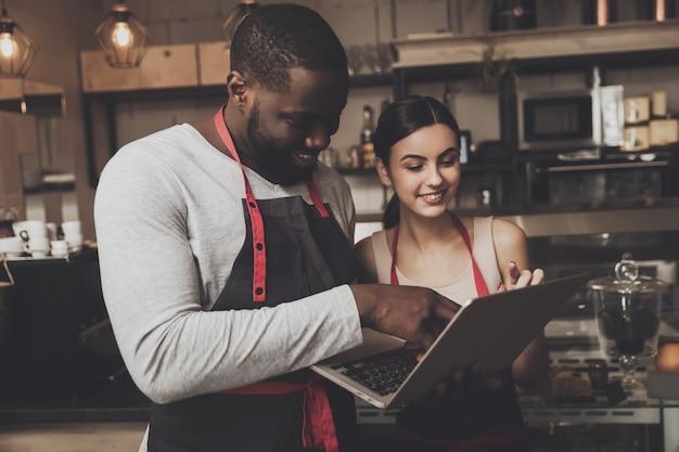 Barista man and woman looking at a laptop Premium Photo