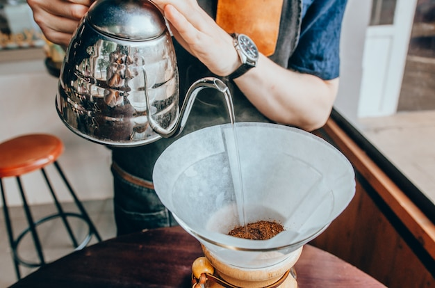 Barista pouring boiling water from kettle Premium Photo