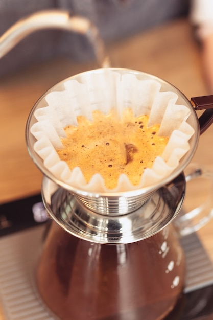 Barista pouring water on coffee ground with filter Free Photo
