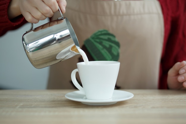 Barista pours milke from steel pot to white cup with coffee Premium Photo