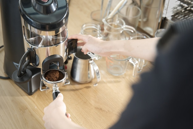 Barista pulling lever of grinder machine to get grind coffee bean in coffee tamp. Premium Photo
