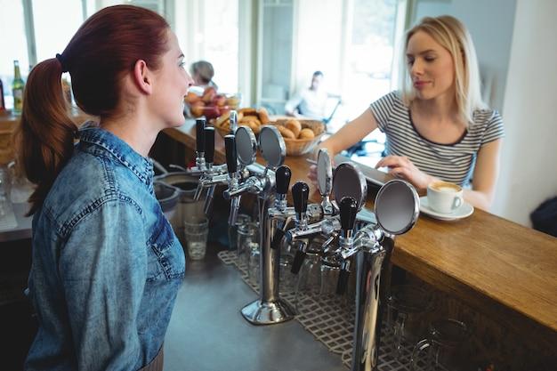 Barista talking with customer at cafe Premium Photo