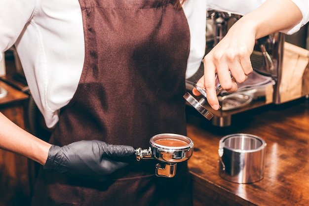 Barista using tamper to makes coffees in coffee bar Premium Photo