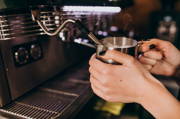 Barista warming up coffee in a coffee machine Free Photo
