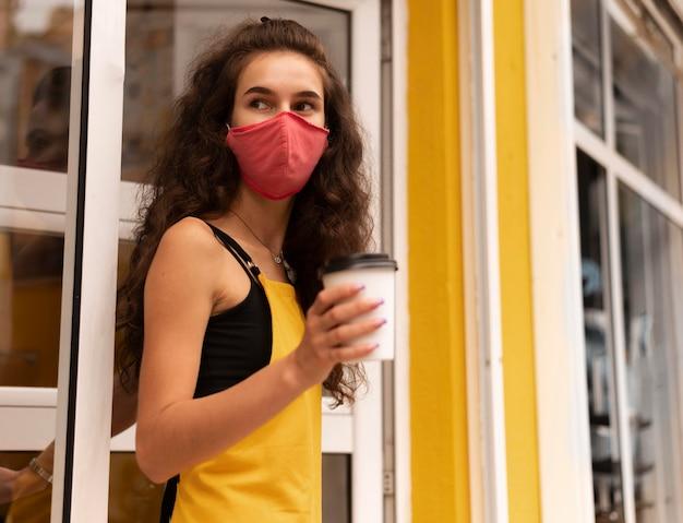 屋外で一杯のコーヒーを保持しながらフェイスマスクを身に着けているバリスタ 無料写真