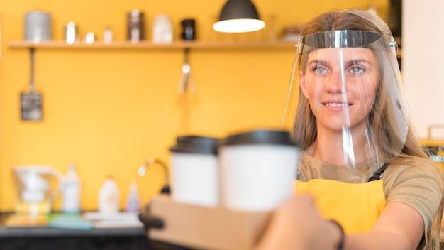Barista che indossa una protezione per il viso quando serve Foto Gratuite