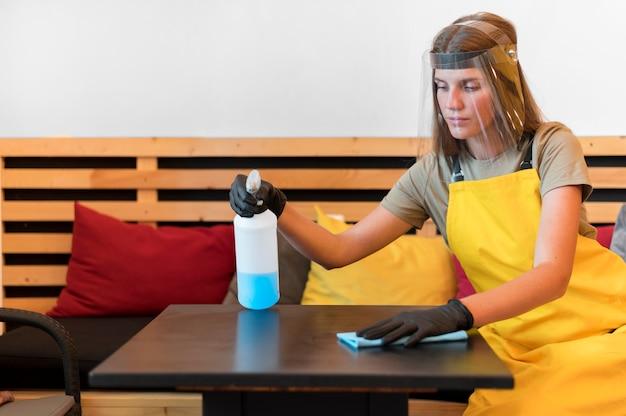 Barista con protezioni per il viso e guanti per la pulizia dei tavoli Foto Gratuite