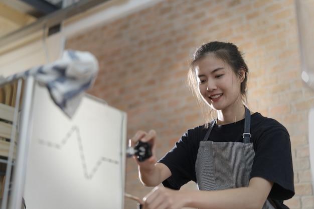 Молодая милая азиатская девушка barista делая кофе в кофейне. Premium Фотографии