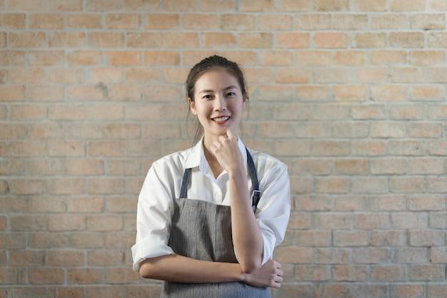 Молодое хорошее смотря азиатское barista стоя в кофейне с красивой кирпичной стеной в предпосылке. Premium Фотографии