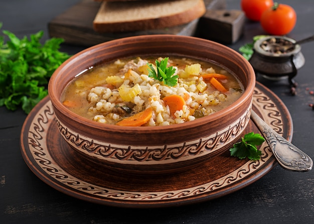 Barley soup with carrots, tomato, celery and meat on a dark surface Free Photo