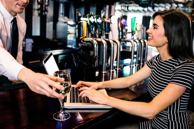 Barman giving a glass of wine at woman using laptop in a bar Premium Photo