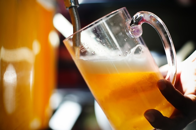 Barman hand at beer tap pouring a draught lager beer serving in the restaurant or pub. Premium Photo