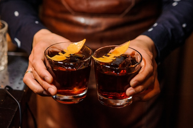 Barman holding two glasses filled with alcoholic drink Premium Photo