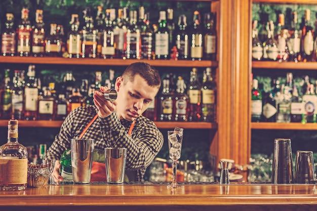 バーテンダーがバーのバーカウンターでアルコールカクテルを作る 無料写真