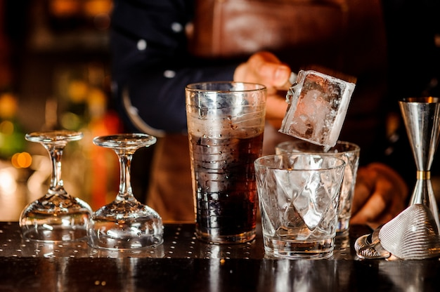 Barman making a cocktail and putting an ice cube into the glass Premium Photo