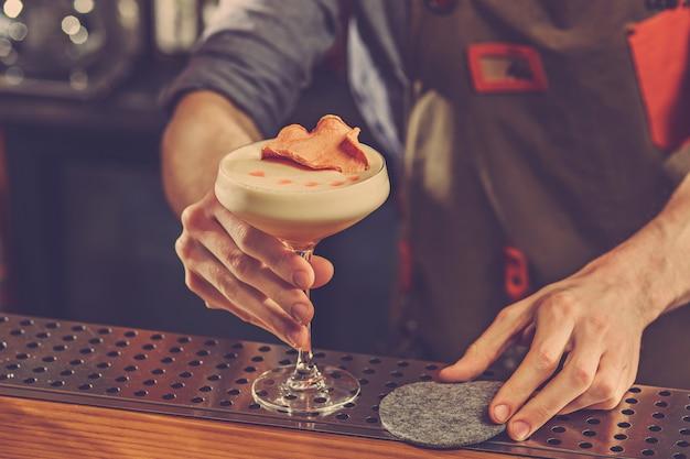 バーのバーカウンターでアルコールカクテルを提供するバーテンダー 無料写真