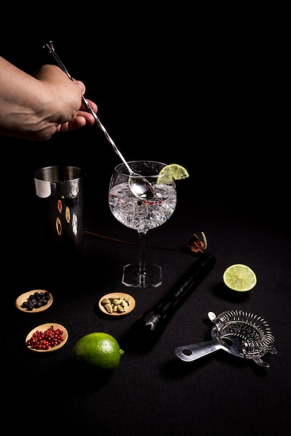 Barman preparing a gin and tonic cocktail on a black background next to his ingredients Premium Photo