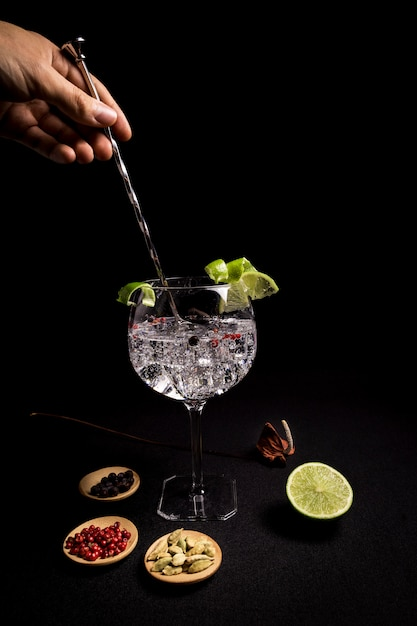 Barman preparing a gin and tonic cocktail on a black background Premium Photo
