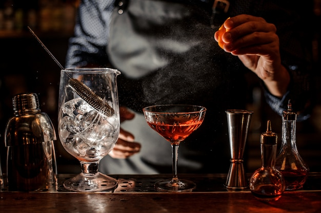 Barman sprinkling fresh orange juice into the cocktail Premium Photo